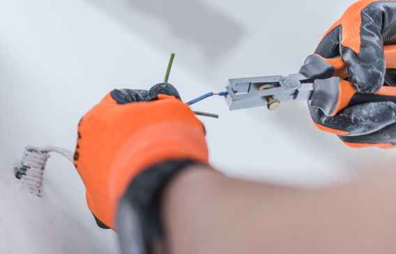 Electrician snipping wires with a pair of pliers and wearing electricial safety gloves