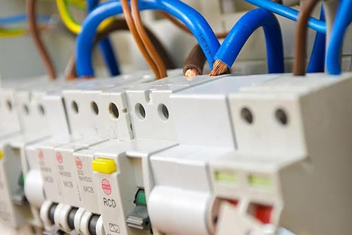 Close up of a consumer unit showing wires and fuse switches