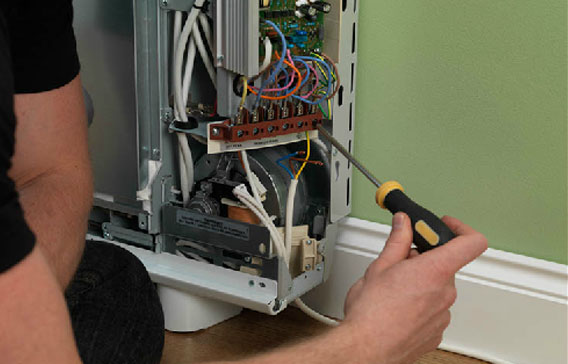 Electrician fixing a broken storage heater radiator with a screwdriver