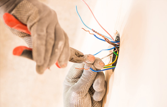 Close up of electricians hands wearing safety gloves and snipping electrical wires with pliers